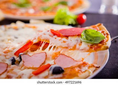 Hot Italian pizza slice with pepperoni and olives and mozzarella cheese drips. A piece of delicious fresh pepperoni pizza on a concrete table