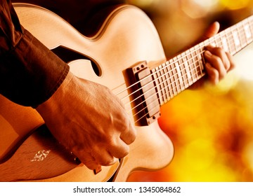 hot jazz guitarist playing guitar live on stage under red lights