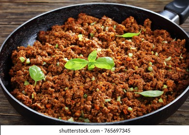 hot juicy ground meat ragout bolognese with tomato sauce, basil, finely chopped vegetables and celery in frying pan on old wooden table, classic recipe, close-up