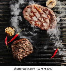 Hot Juicy Ribeye Steak on Barbecue Grill Background. Fresh Beef Steaks with Grilled Garlic, Spices and Red Peppers. Bbq Entrecote Meat Top View