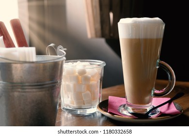 Hot late coffee in transparent glass on table and sunrays from window