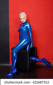 hot latex rubber blue catsuit woman on red wall