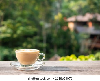 Hot latte art coffee in morning on wooden table with natural backgrounds.