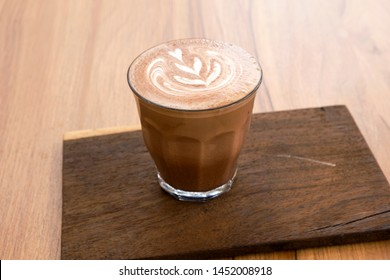Hot latte and beautiful art latte on wooden floors