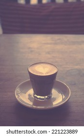 hot latte or cappuccino coffee on wooden desk with retro filter effect or instagram filter