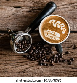 Hot latte coffee in black cup  and coffee brew holder on weathered wood table with coffee beans