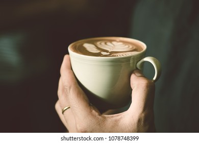Hot latte coffee cup in barista hand, ready to serve for customer, vintage film effect