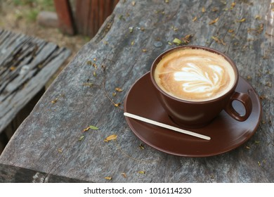 Hot latte coffee cup on wooden table