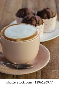 A hot latte coffee served in a beige cup with chocolate muffins in a gourmet cafe