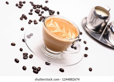 Hot latte coffy in a clear glass on a white background with coffee beans.