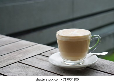 Hot Latte - Cup of coffee with beautiful latte art on wooden table background and copy space, Morning Breakfast.