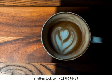 Hot Latte half cup on a Wooden Table