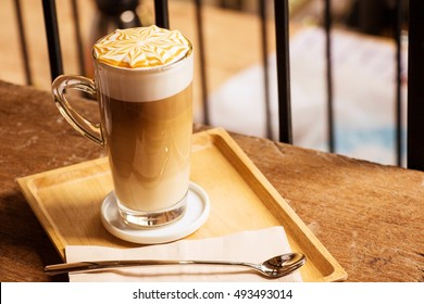 Hot latte macchiato coffee  with caramel arts on the top serving with tall clear glass