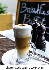 Hot latte macchiato coffee with tasty foam and cinnamon in tall clear glass on serving table