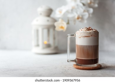 Hot latte macchiato with delicious foam in a tall transparent glass on an easy table setting. Photo in a high key. Breakfast time. Rustic background.