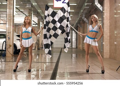 Hot leggy models with race flags at car wash
