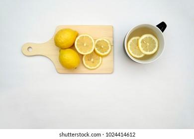 Hot lemon tea and lemons isolated on a white background.