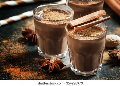 Hot liquid chocolate with warming winter spices, cinnamon, anise and nutmeg, selective focus