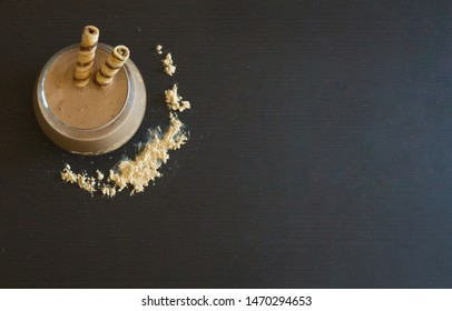 A hot maca latte, made with maca powder, cocoa powder, and milk. A Peruvian superfood good for hormone regulation. On a black background with copy space, and maca powder sprinkled around the glass.