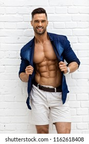 Hot male model with six pack posing over white background