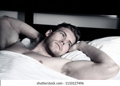 Hot male, naked in bed, between white sheets, he is looking at and playing with the camera.