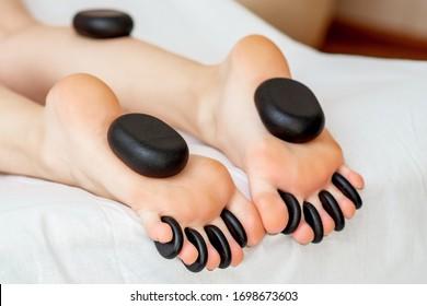 Hot massage stones on feet of woman while leg massage close up.