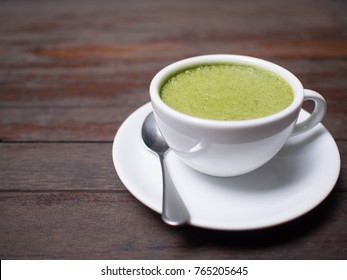 Hot matcha green tea latte with milk foam in a white cup and plate on old wooden table. Japanese beverages. Selective focus.