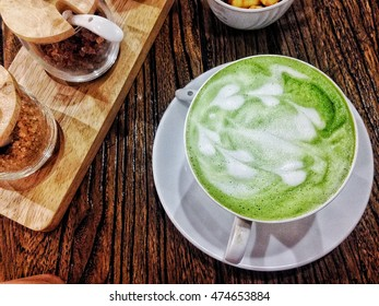Hot Matcha vanilla in white cup and sugar in bottles,put on wood table,top view