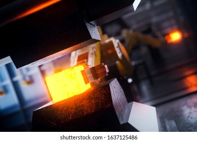 Hot metal billet under the press. Conveyor line of a plant for the production of metal products.