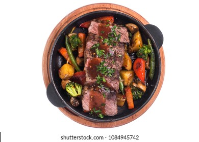 Hot metal pan with roast beef and vegetables isolated on a white background. top view