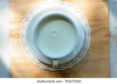Hot milk in ceramic cup on wooden table