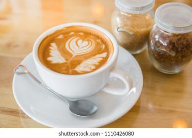 Hot milk latte art coffee on wooden table, Vintage latte art coffee