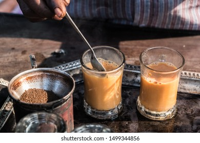 Hot milky tea in glasses being stirred on a tray at a tea stall.