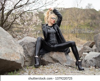 Hot mistress in latex suit and vinyl coat is sitting on rocks
