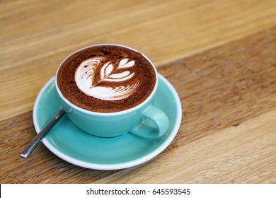 Hot Mocha - A Cup of Coffee with Beautiful Latte Art on wooden table background, Morning Breakfast.