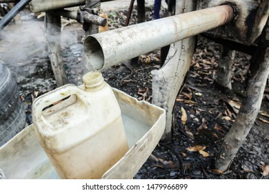 Hot moonshine flows from the pipe into the canister.