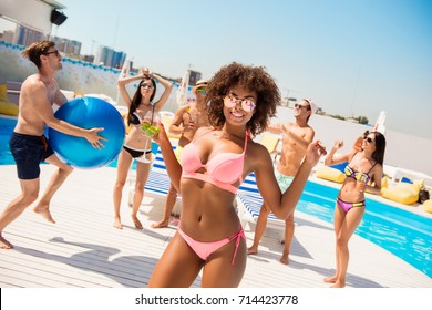 Hot mulatto chic with mohito is posing, dancing at the beach pool disco party, enjoying, chilling with friends, they play ball, with huge ribbon blue baloon, at the roof top resort with great view