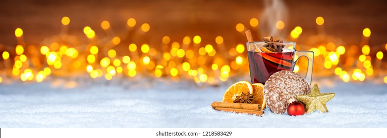 hot mulled spiced red wine in glass mug with gingerbread orange slice christmas market xmas decoration illuminated bright lights bokeh panorama wide background