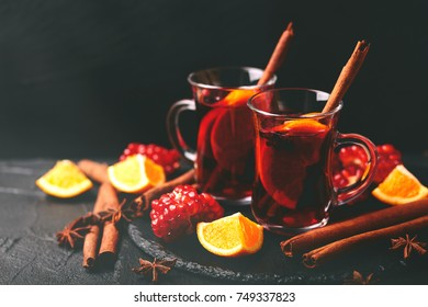 Hot mulled wine with apples, pomegranate, orange, anise and cinnamon with fresh fruits on slate marble background. Flat lay, copy space, horizontal view. Christmas and holidays food