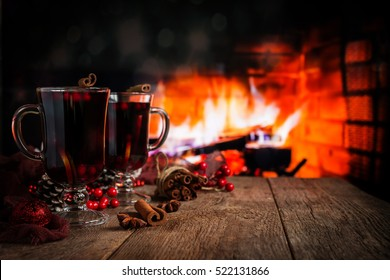 Hot mulled wine in a glass with orange slices, anise and cinnamon sticks on vintage wood table. Fireplace as background. Christmas or winter warming drink.