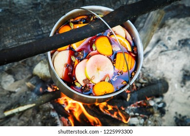 Hot mulled wine (gluhwein) in the cauldron over the bonfire. A hot wholesome traditional fruit drink.