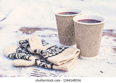 Hot mulled wine and knitted gloves on the snow with snowflakes effect