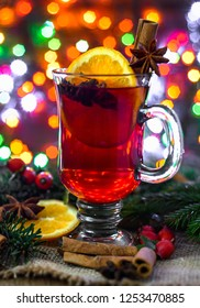Hot mulled wine on christmas lights background. Winter grog with spices.