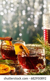 Hot mulled wine on decorative glasses with slices of orange, Christmas bokeh background.