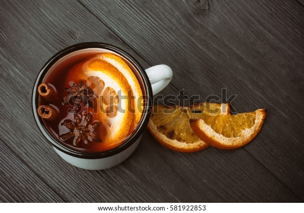 Hot mulled wine on a wooden background, with spices and orange.