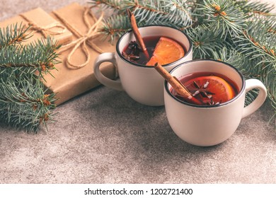 Hot mulled wine in a small vintage cups with christmas tree and present. Christmas or winter warming drink. Horizontal view. Copy space