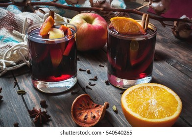 Hot mulled wine with spices, apple and orange on wood background