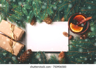 Hot mulled wine with spices, Christmas tree, gifts and cones on marble background. To do list. Planning and design conceptFlat lay, copy space, top view.