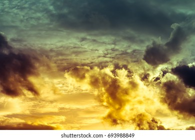 Hot orange clouds and yellow light on overcast sky