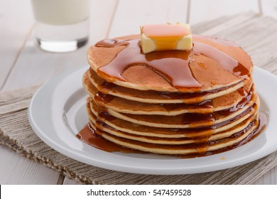 Hot pancakes make butter melt. Maple syrup is flowing down the stack. Mouth-watering still-life of American morning meal.